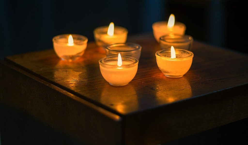 Five lit candles sit in glass containers on a wooden surface.